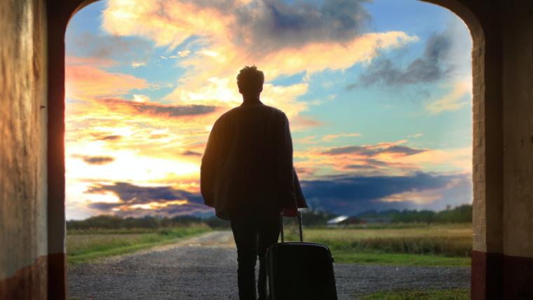 スーツケースをもって旅行に行く人